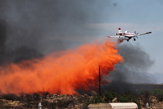 An airplane dunks flame retardant on a brush fire near Tombstone, on May 13, 2013.